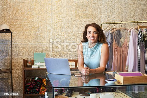istock Young woman working in clothes shop leaning on counter 638778044
