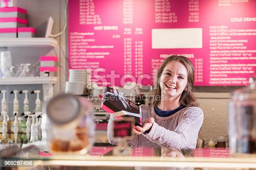 istock Young woman working in coffee shop handing box over 969287456