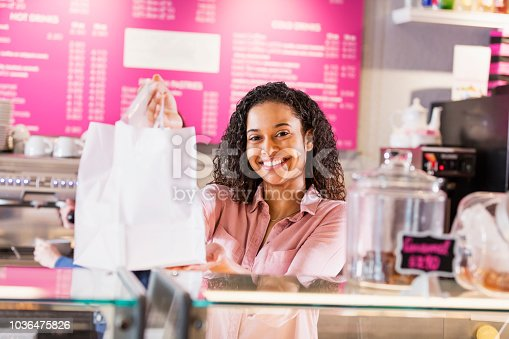 istock Young woman working in coffee shop handing shopping bag 1036475826