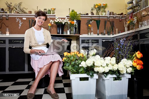 Small business - woman with trays of fresh cut flowers, taking inventory on laptop
