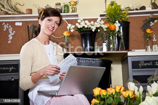 Small business owner paying bills on laptop