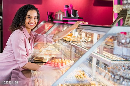 istock Young woman working in pastry shop with french macarons 1023224128