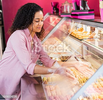 istock Young woman working in pastry shop with french macarons 1023224220