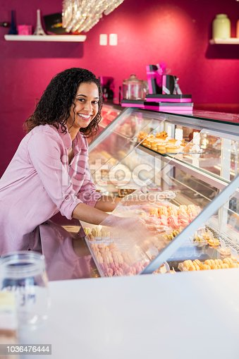 istock Young woman working in pastry shop with french macarons 1036476444