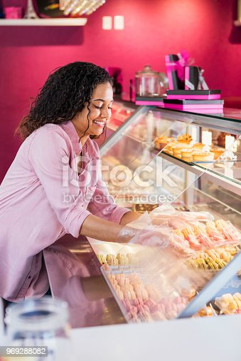 istock Young woman working in pastry shop with french macarons 969288082