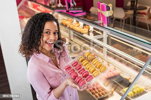 istock Young woman working in pastry shop with french macarons 969288294