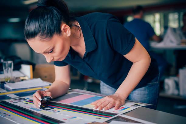 Mulher jovem trabalhando na fábrica de impressão - foto de acervo