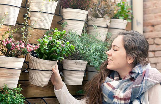 junge frau arbeiten im blumen-shop - paletten terrasse stock-fotos und bilder