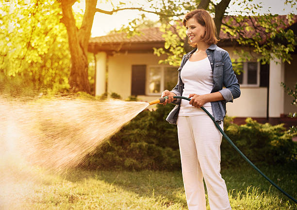 young woman working in the garden - garden hose stock pictures, royalty-free photos & images