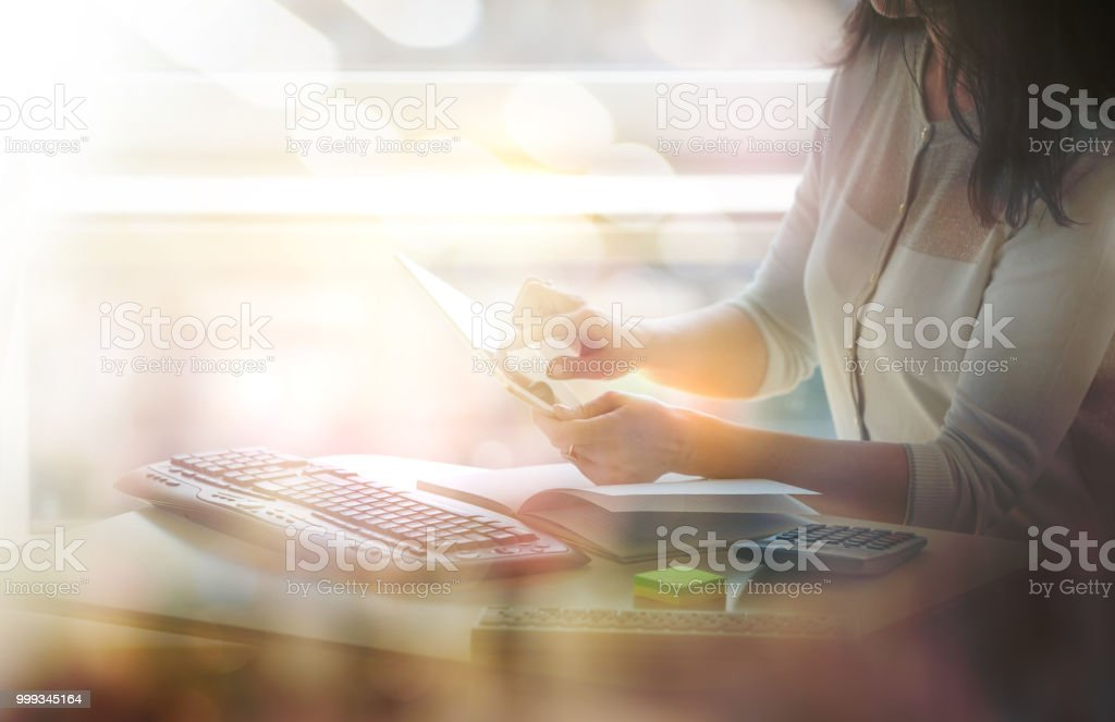 Young woman working in the office. Close up of businesswoman hands holding pen, working on calculator and keyboard, calculate business data. Charts and graphs at the background stock photo