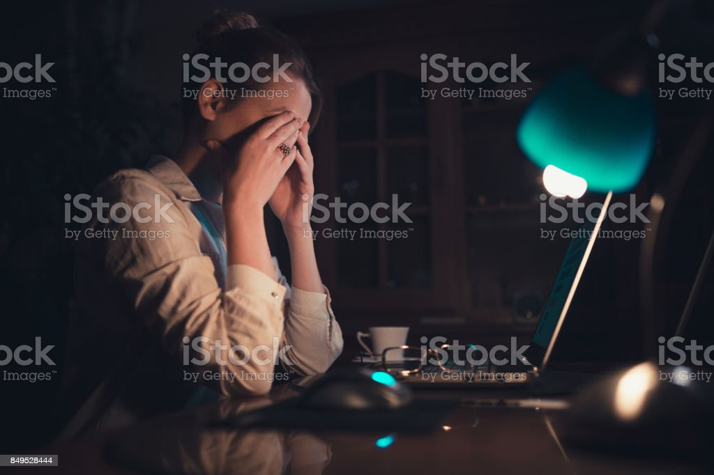 Young woman working late at home stock photo