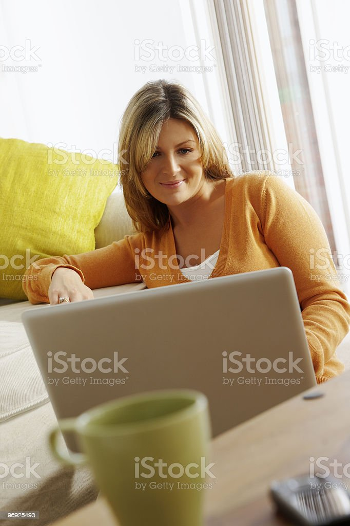 young woman working on a laptop computer at home royalty-free stock photo