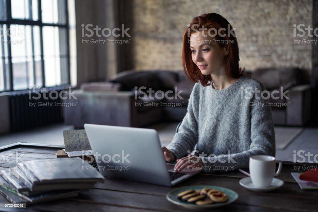 Junge Frau, die arbeitet auf einem Laptop in einem Loft-Wohnung – Foto