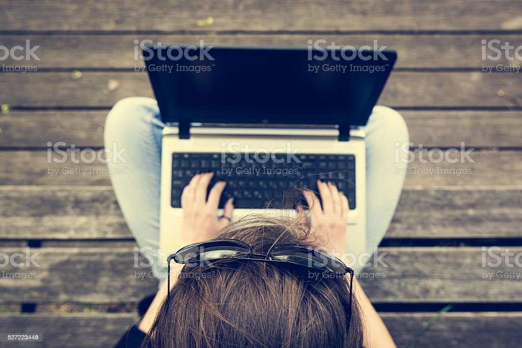 Young woman working on a laptop. View from above. stock photo