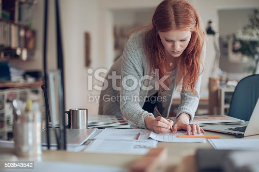 506821756 istock photo Young woman working on a project 503543542