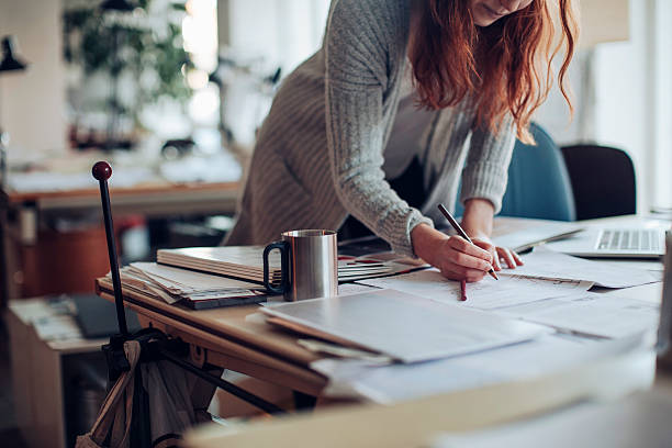 Young woman working on a project Close up of a designer working on a project messy home office stock pictures, royalty-free photos & images