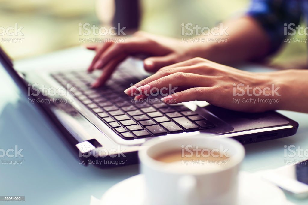 Young woman working on computer outdoors stock photo