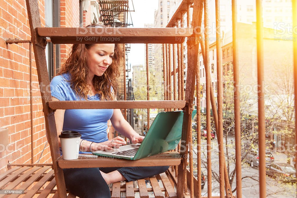 young woman working on computer siting on fire escape stock photo