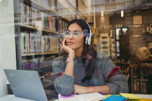 jovem mulher a trabalhar em seu laptop na biblioteca - college people laptop - fotografias e filmes do acervo