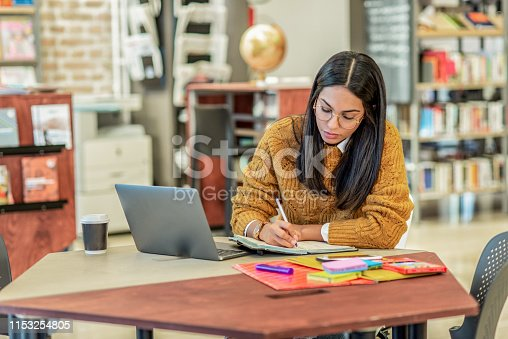 istock young woman working on her laptop in the library 1153254805