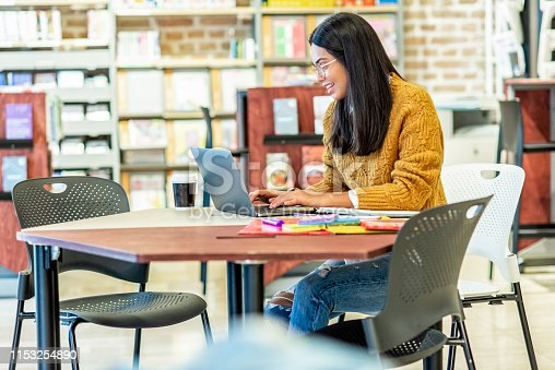 istock young woman working on her laptop in the library 1153254890