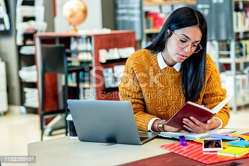 istock young woman working on her laptop in the library 1153255151