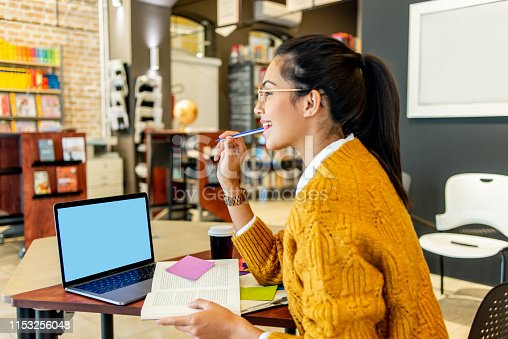 istock young woman working on her laptop in the library 1153256048