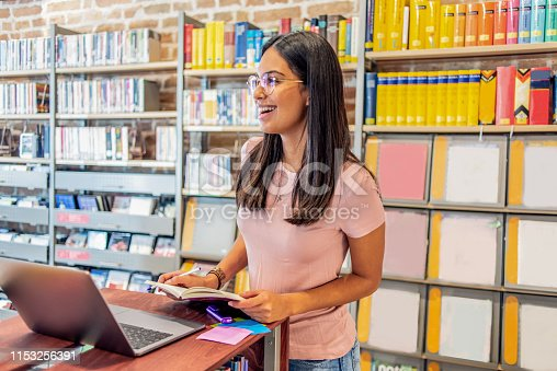 istock young woman working on her laptop in the library 1153256391