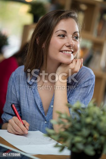 694187664 istock photo Young woman working on her tablet in a coffee shop 621475998