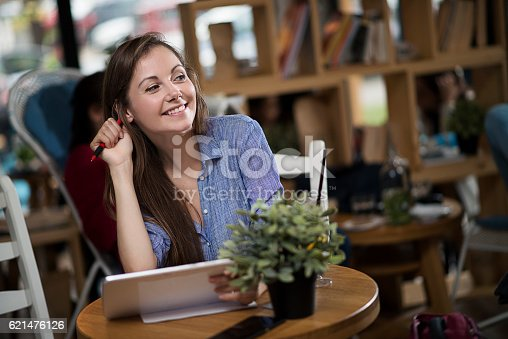 694187664 istock photo Young woman working on her tablet in a coffee shop 621476126