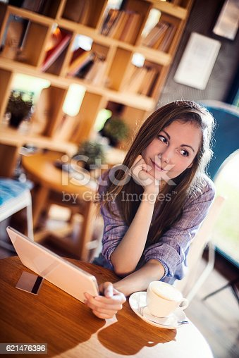 694187664 istock photo Young woman working on her tablet in a coffee shop 621476396
