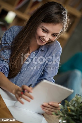 694187664 istock photo Young woman working on her tablet in a coffee shop 622442216