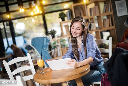 694187664 istock photo Young woman working on her tablet in a coffee shop 638071984