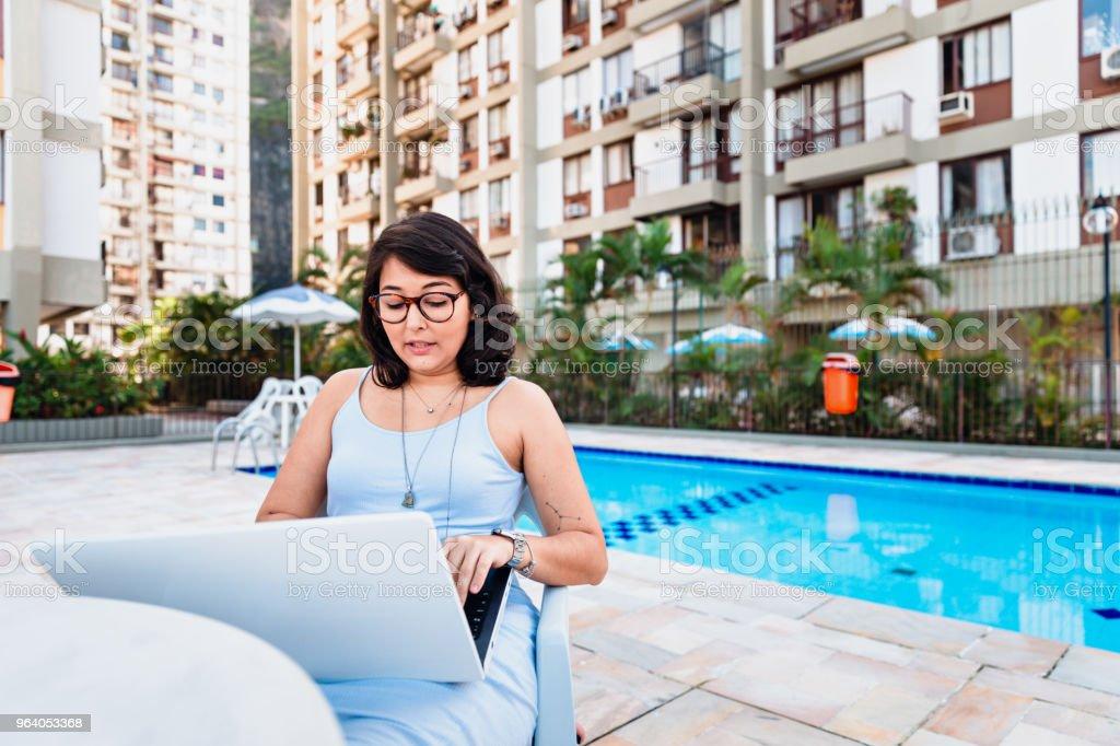 若い女性に取り組んでいるノートパソコンのプールサイド - 1人のロイヤリティフリーストックフォト