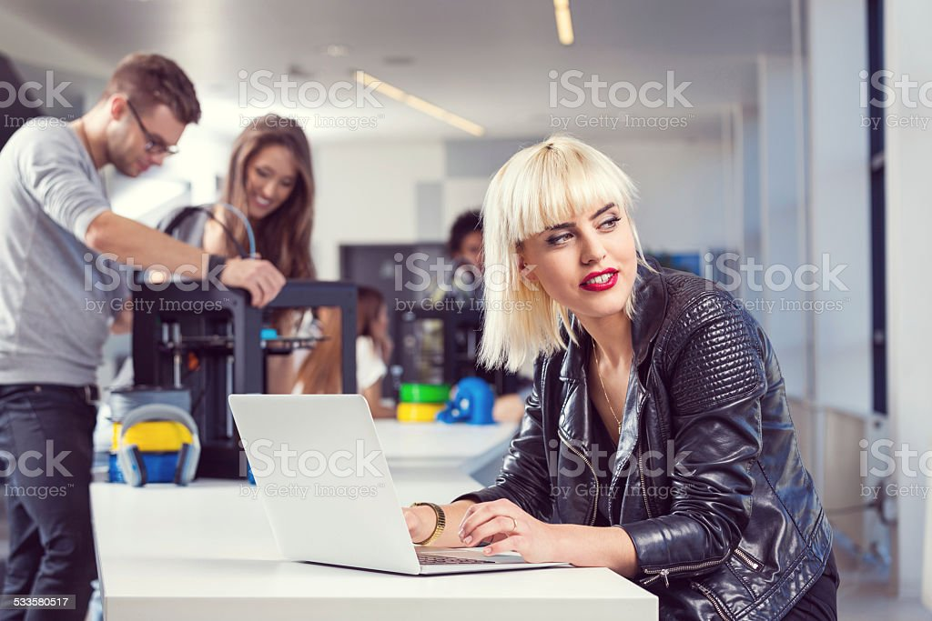 Young woman working on laptop in 3D printer office Young woman wearing leather jacket working on computer in an office, with her coworkers using a 3D printers in the background.  2015 Stock Photo