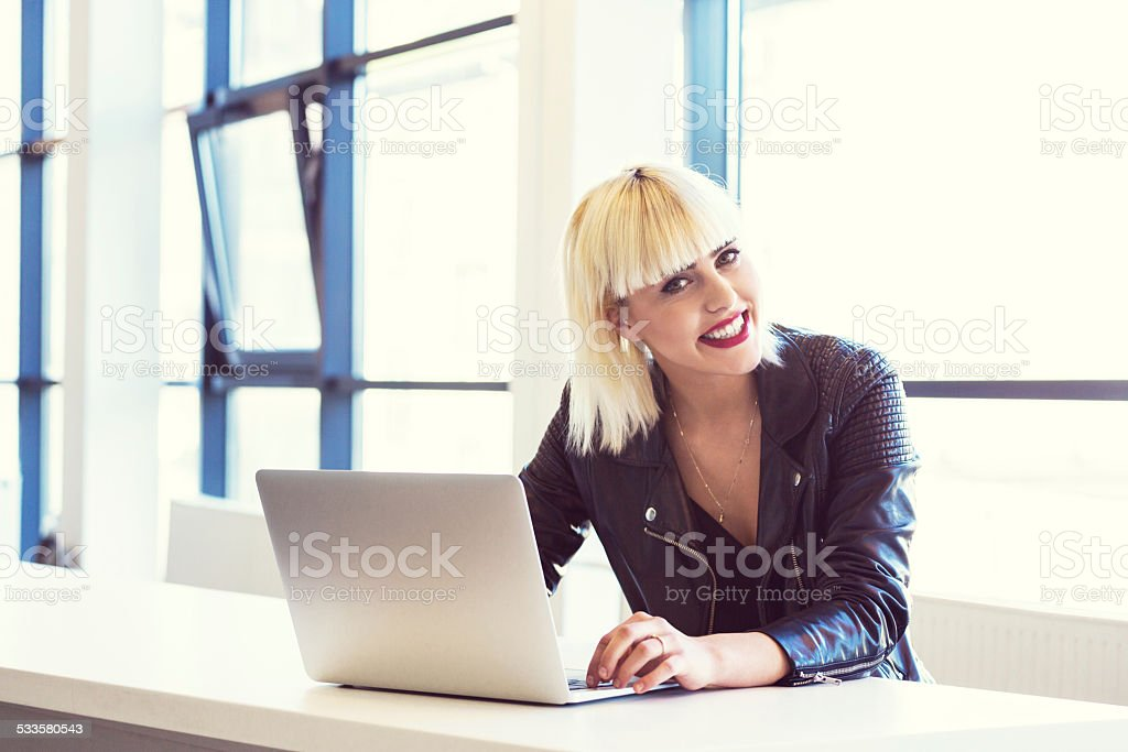 Young woman working on laptop in an office Young blond woman wearing leather jacket working on computer in an office, smiling at camera. 20-24 Years Stock Photo