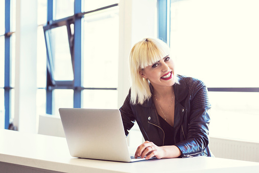 Young Woman Working On Laptop In An Office Stock Photo - Download Image Now