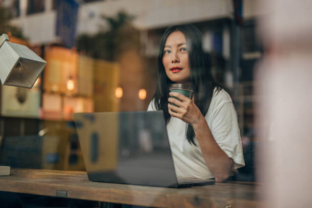 Young woman working on laptop in cafe stock photo