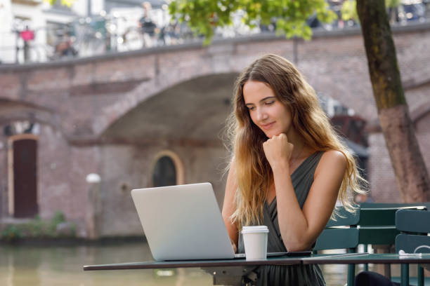 Young Woman Working On Laptop Outdoors stock photo