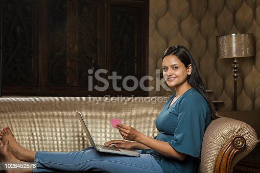 637756964 istock photo Young woman working on laptop - Stock image 1028452576