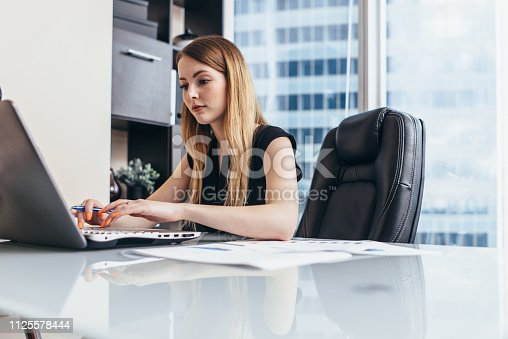 istock Young woman working on laptop studying financial data and statistics of the company 1125578444
