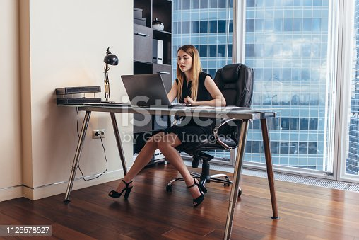 istock Young woman working on laptop studying financial data and statistics of the company 1125578527