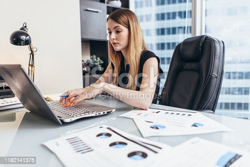 istock Young woman working on laptop studying financial data and statistics of the company 1162141375