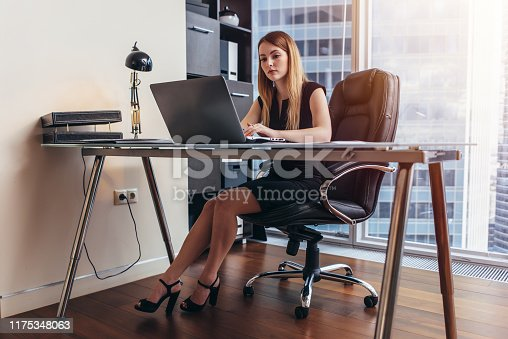 istock Young woman working on laptop studying financial data and statistics of the company 1175348063