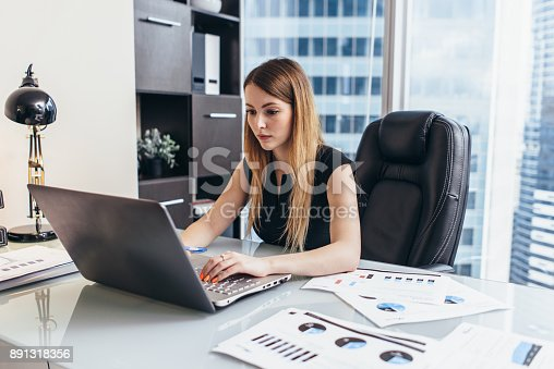 istock Young woman working on laptop studying financial data and statistics of the company 891318356
