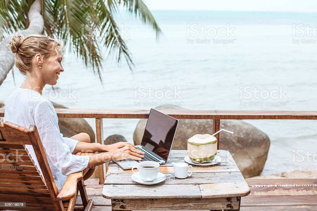 Young woman working on laptop with coffee and young coconut royalty-free stock photo