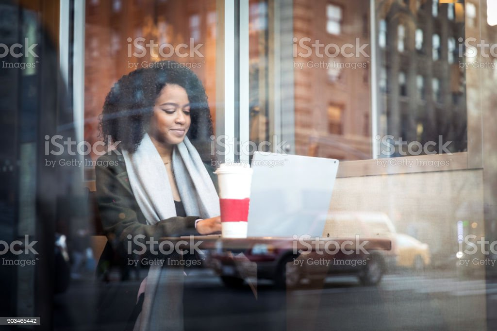 Young woman working on the move at cafe stock photo