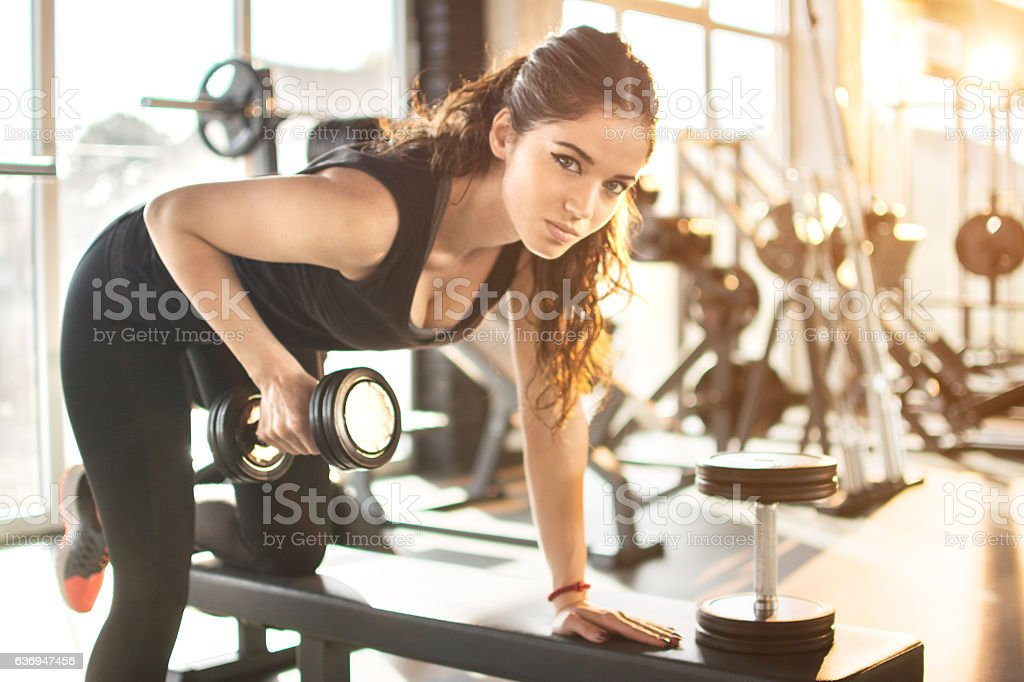 Young woman working out in gym and lifting weights. - foto de stock