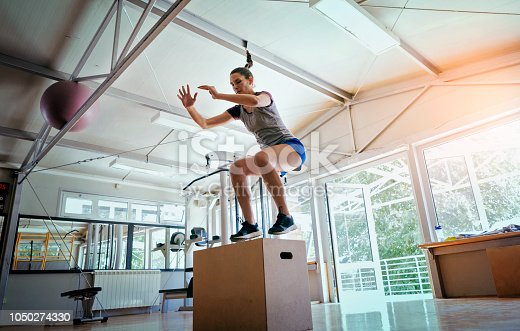 Young woman jumping on box in gym