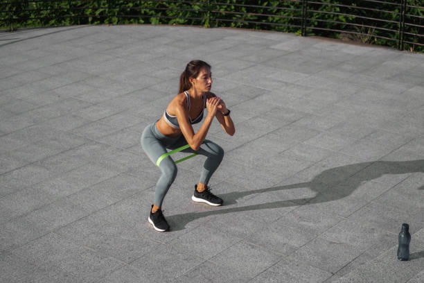 Young woman working out with an exercize band outside stock photo